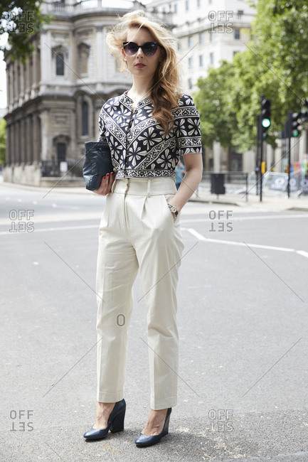 London, England - June 11, 2017: White woman with long blonde hair and sunglasses wearing black and white patterned short sleeve blouse and white trousers standing in the street during London Fashion Week Men's