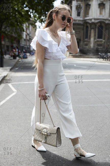 London, England - June 11, 2017: White woman dressed in white clothes and sunglasses holding designer handbag walking in the street during London Fashion Week Men's