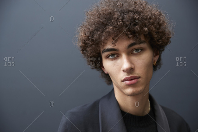 London, England - June 11, 2017: Close up portrait of mixed race young male fashion model against black wall during London Fashion Week Men's