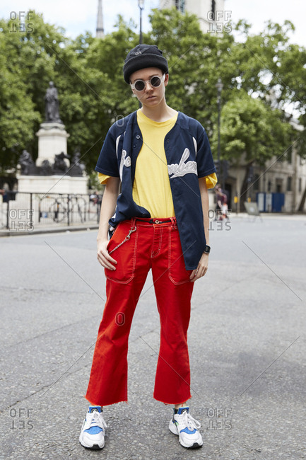 London, England - June 11, 2017: Young white man in red trousers and baseball shirt standing in the street during London Fashion Week Men's