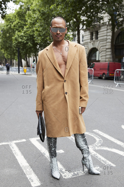 London, England - June 11, 2017: Bare chested man wearing camel coat and high heel snakeskin boots in the street during London Fashion Week Men's