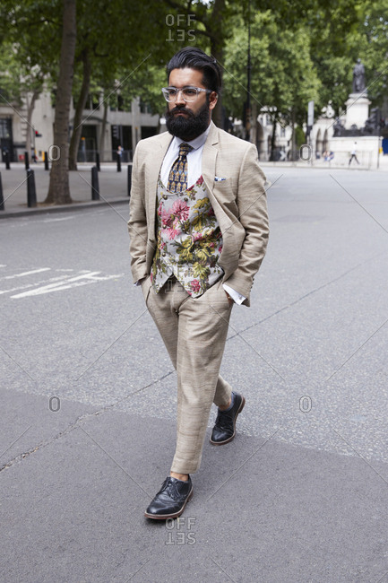 London, England - June 11, 2017: Bearded Asian man wearing glasses and suit with floral waistcoat walking in the street during London Fashion Week Men's