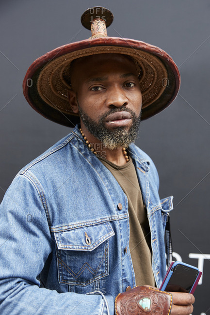London, England - June 11, 2017: Bearded black man wearing a straw hat in the street during London Fashion Week Men's