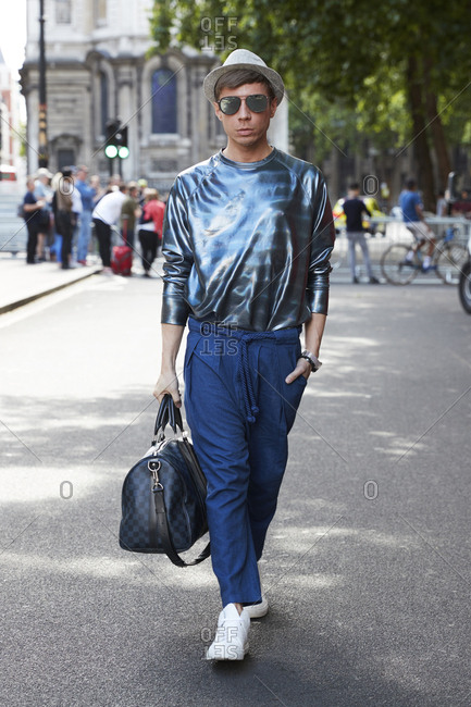 London, England - June 11, 2017: White man wearing shiny metallic top and blue baggy trousers walking in the street carrying hold all during London Fashion Week Men's