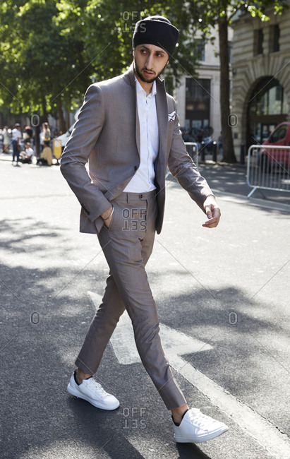 London, England - June 11, 2017: Young British Asian Sikh wearing a turban and fashionable skinny suit walking in the street during London Fashion Week Men's
