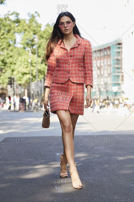 London, England - June 11, 2017: Fashion blogger Doina Ciobanu walking in the street wearing a pink checked mini skirt suit during London Fashion Week Men's