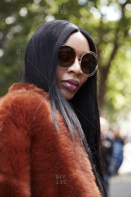 London, England - June 11, 2017: Black woman wearing brown faux fur jacket and sunglasses in the street during London Fashion Week Men's