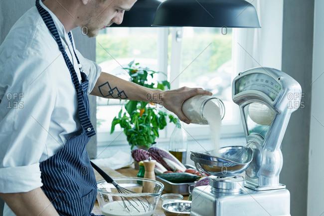 Male chef, weighing ingredients on vintage scales
