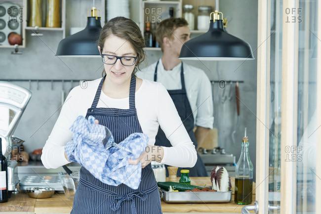 Portrait of female caterer, polishing wine glasses, smiling