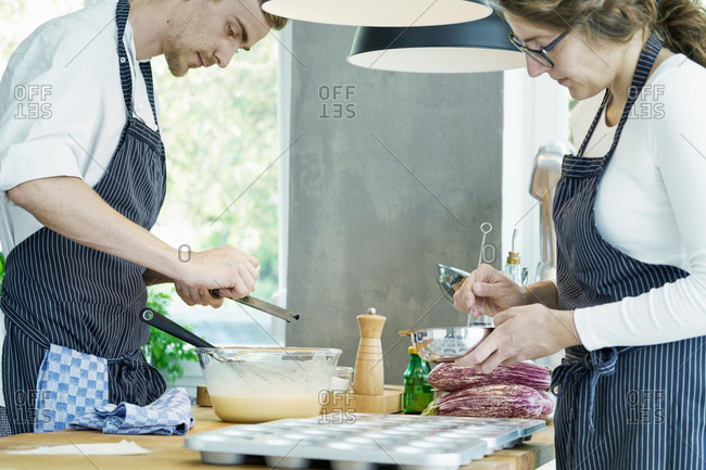 Two chefs working at table, preparing food