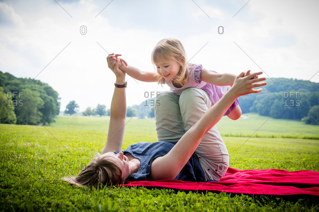 Mid adult woman lying on back balancing daughter in rural field