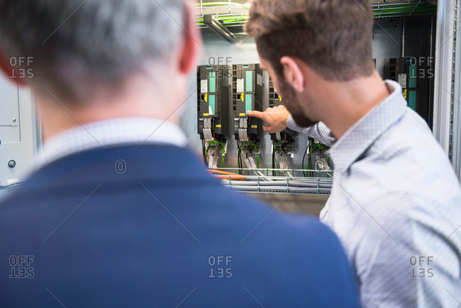 Businessmen in factory inspecting control panel
