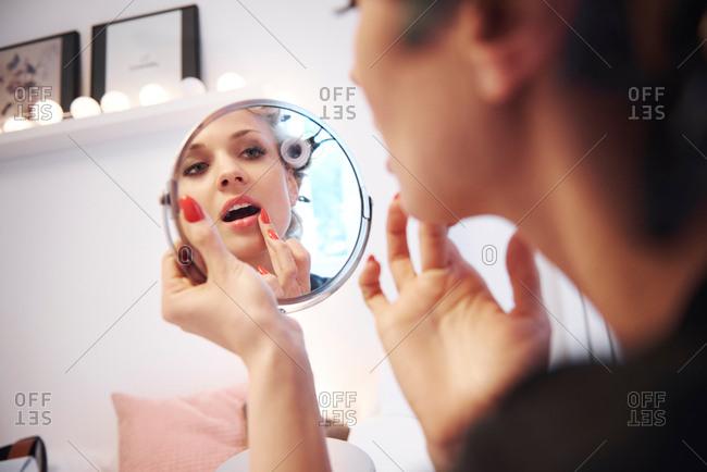 Mirror image of woman applying lipstick