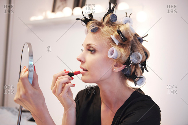 Woman with hair rollers applying lipstick in mirror