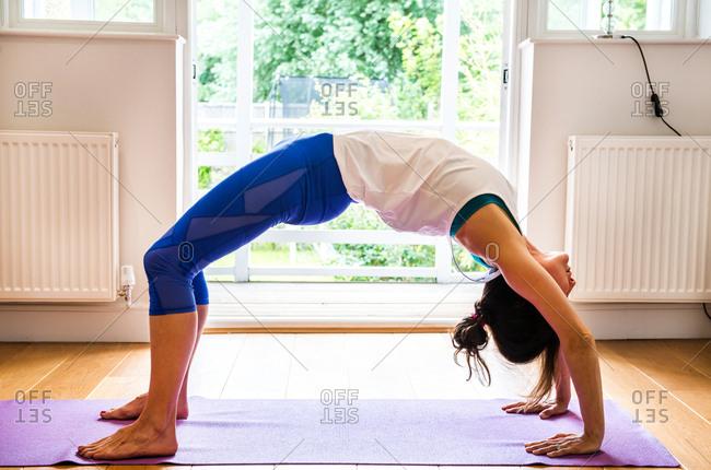 Woman bending over backwards in yoga position