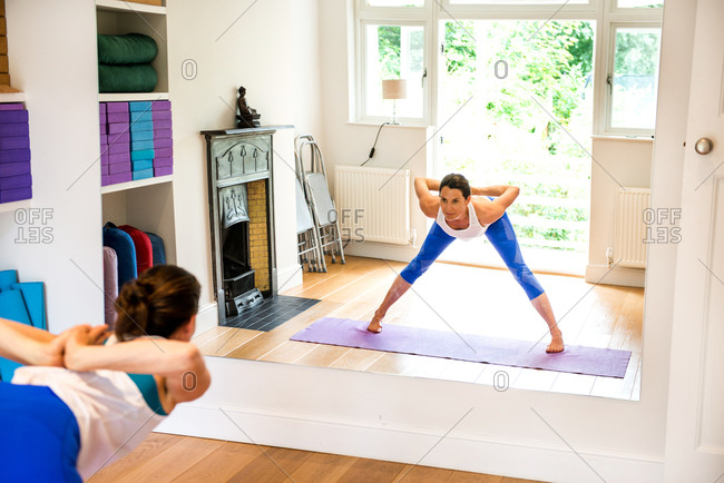 Mirror image of woman bending forward in yoga position