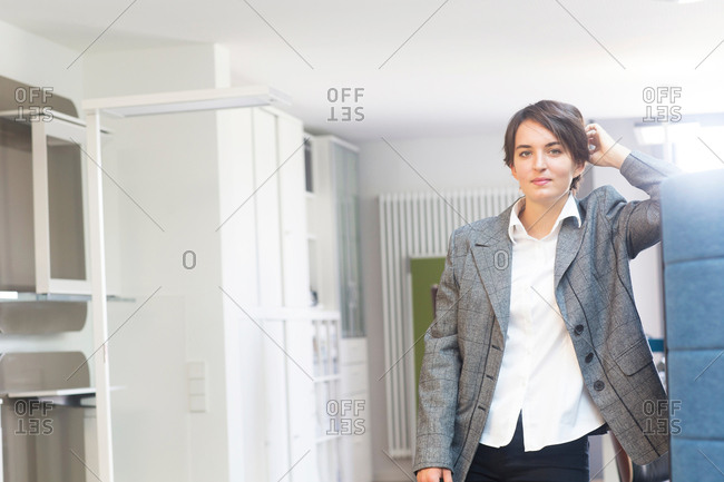 Portrait of young female sales manager leaning against office partition in office furniture store