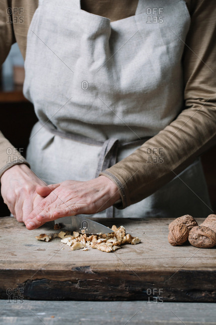 Woman chopping walnuts on chopping board, using knife, mid section