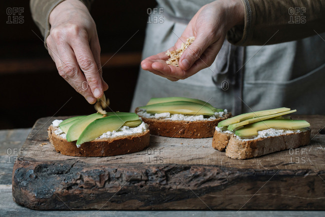 Woman sprinkling chopped walnuts onto avocado bruschetta, mid section