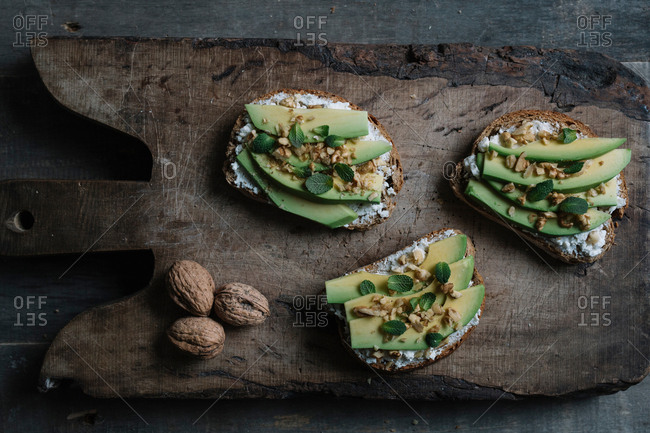 Still life of ricotta, avocado and walnut bruschetta on chopping board, overhead view