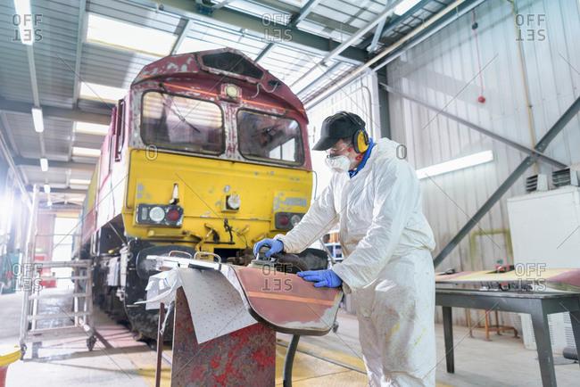 Painter preparing surface of refurbished locomotive in paint shop in train works