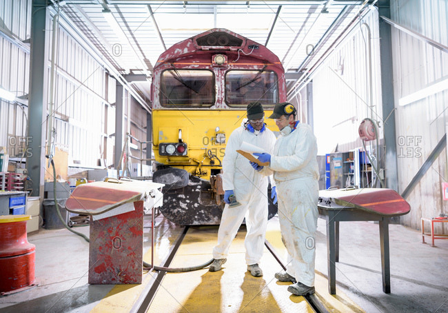 Painters in paint shop with refurbished locomotive in train works