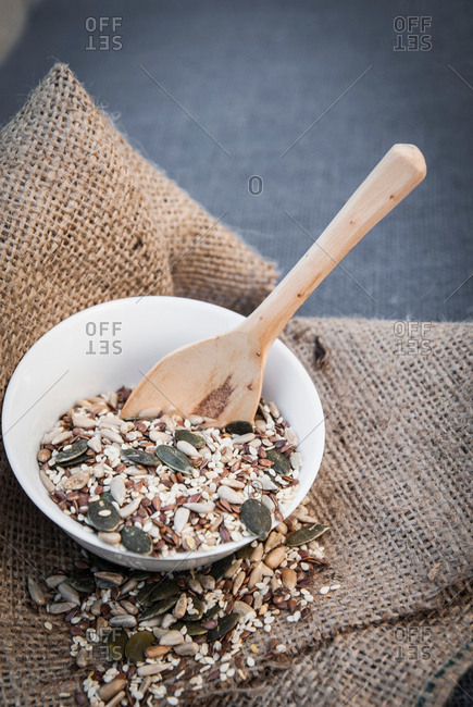 Selection of seeds in bowl with wooden spoon, close-up
