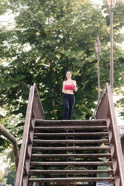 Young female runner running across footbridge