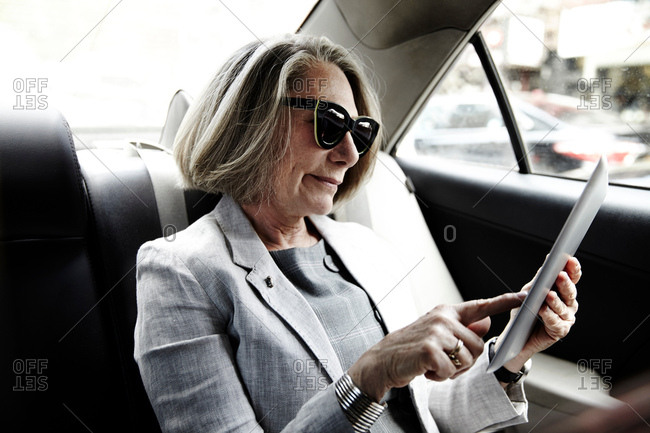 Senior businesswoman sitting in back of taxi, using digital tablet