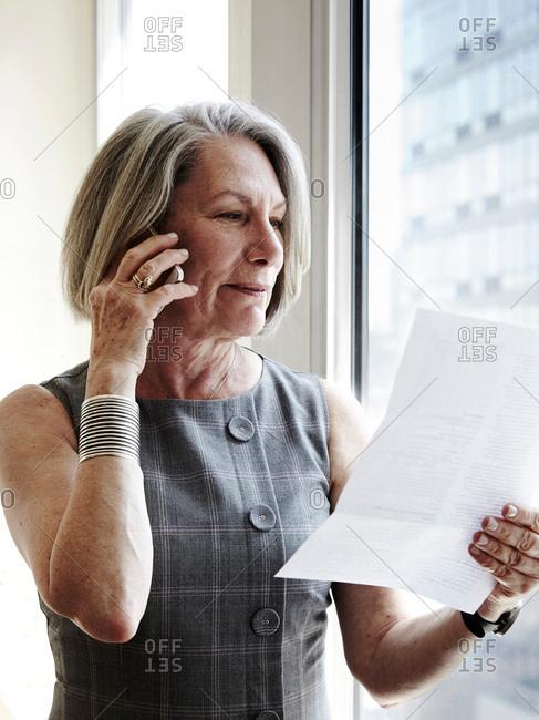 Senior businesswoman using smartphone, reading document