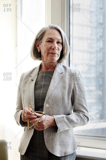 Portrait of senior businesswoman holding eyeglasses