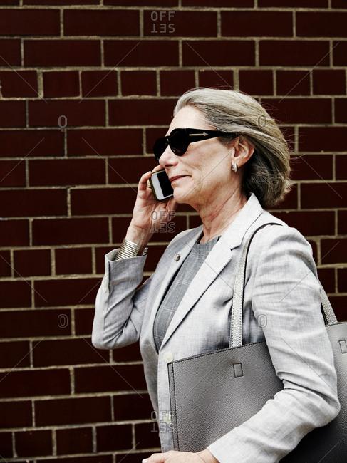 Senior businesswoman walking in street, speaking on smartphone