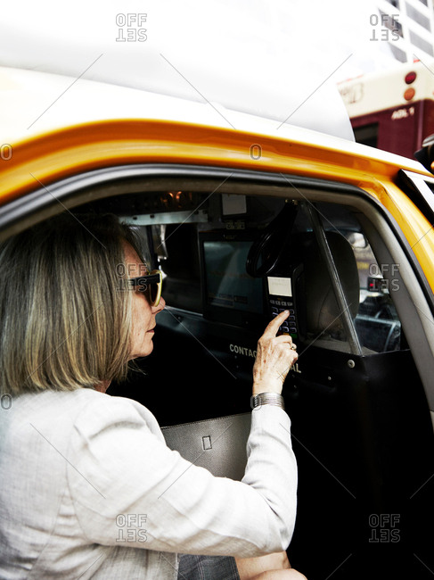 Senior businesswoman in back of taxi, making payment for journey with payment machine