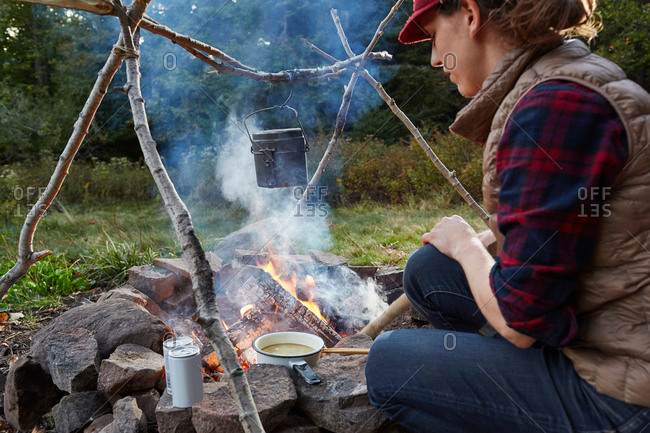 Woman sitting beside camp fire, cooking food, Colgate Lake Wild Forest, Catskill Park, New York State, USA