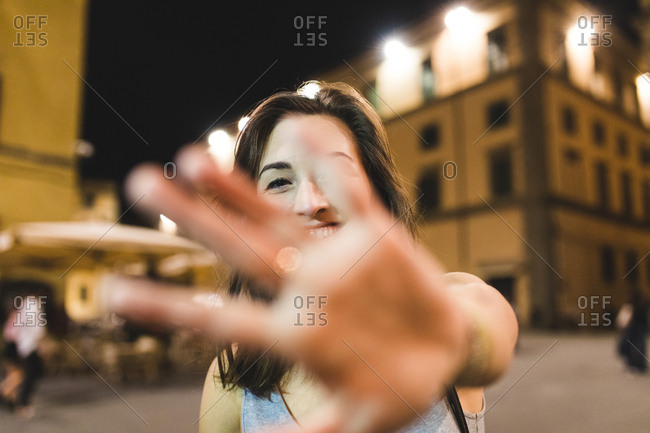Portrait of young woman in city at night, palm up to camera