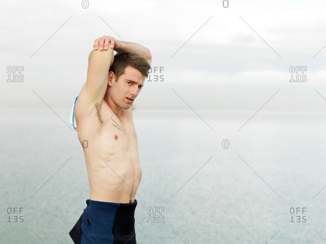 Bare chested man warming up, stretching arms, Melbourne, Victoria, Australia, Oceania