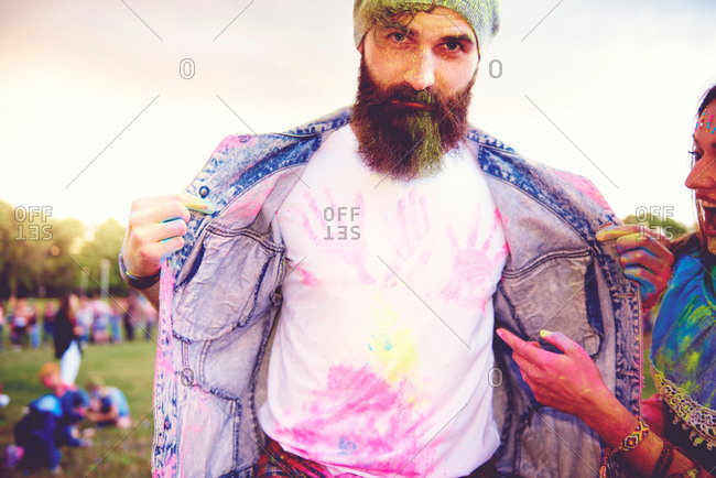 Portrait of young male hipster with chalk handprints on t-shirt at festival