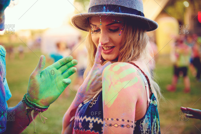 Young woman with green handprint on shoulder and boyfriend chalked hand at festival