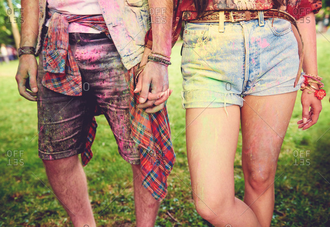 Waist down view of young couple covered in colored chalk powder at festival