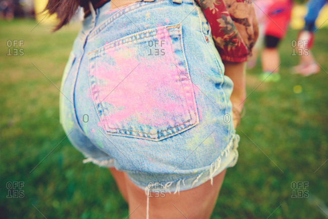 Cropped view of young woman's denim shorts with pink chalk handprint on buttock at festival