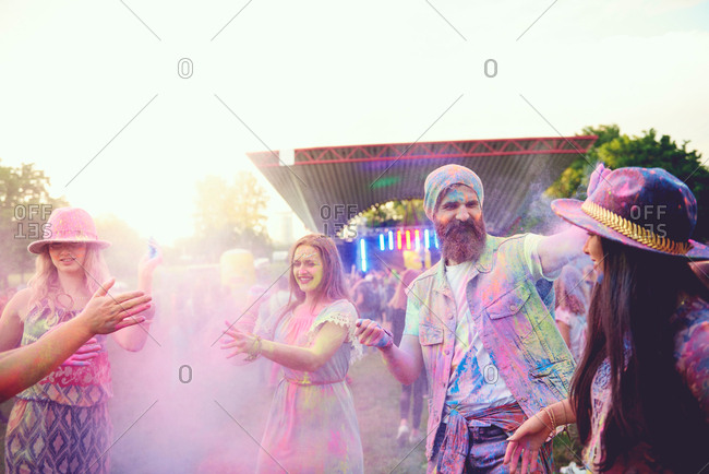 Young adult friends dancing and throwing colored chalk powder at festival