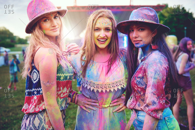 Portrait of three young boho women covered in colored chalk powder at festival