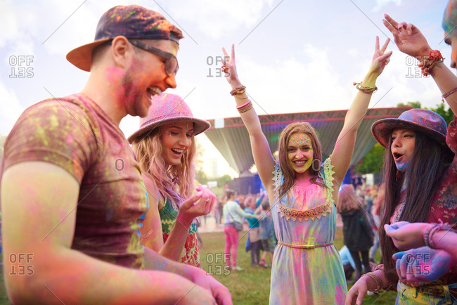 Young adult friends dancing covered in colored chalk powder at festival