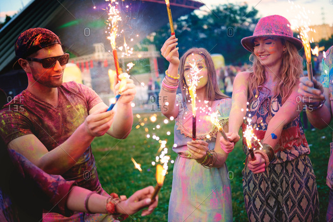 Young adults covered in colored chalk powder holding sparklers at festival
