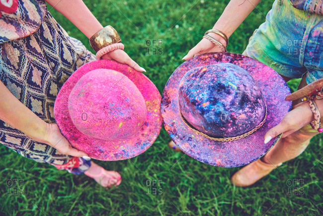 Waist down view of two young women holding felt hats covered in colored chalk at festival