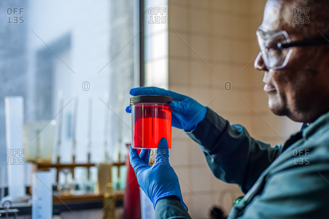 Lab technician looking at beaker of red biofuel in biofuel plant laboratory