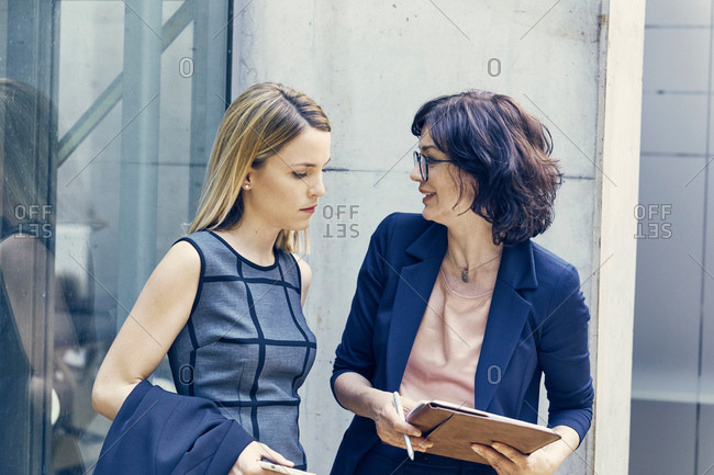 Two businesswomen discussing paperwork in office