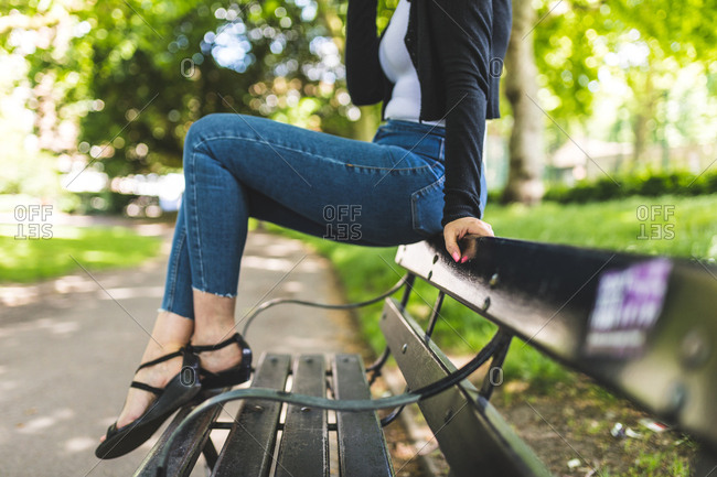 Neck down view of woman sitting on top of park bench