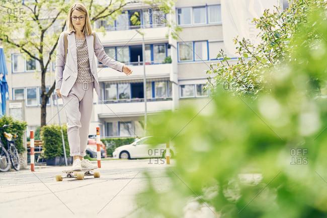 Businesswoman skateboarding to work