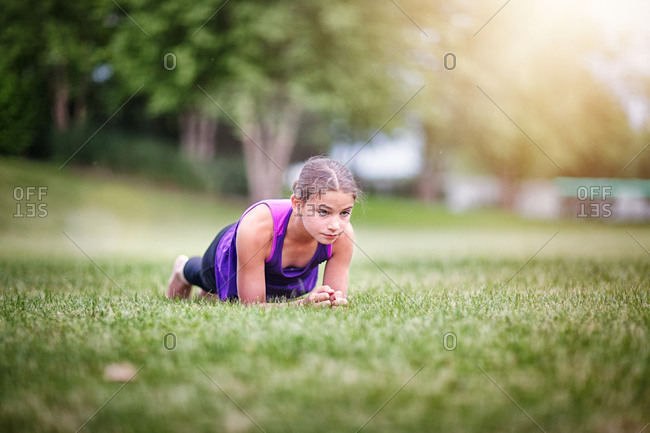 Girl in plank position on grass
